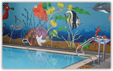 Mural of cartoon fish on wall behind pool